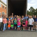 Local congregation standing in front of a moving truck